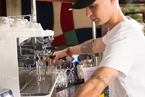 Young tattoed barista in the coffee shop making coffee using com