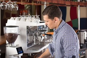Young handsome barista making coffee using commercial grade coff