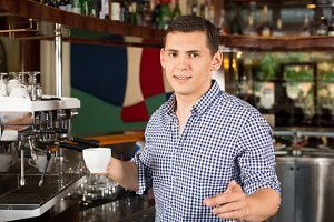 Handsome smiling barista holding a cup of coffee and pointing fi