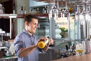Happy smiling bartender pouring drink into a steel jigger.