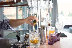 Bartender holding steel jigger and pouring orange liquor into th