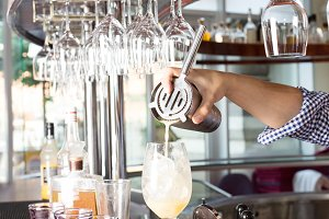 Bartender holding steel shaker up and pouring mixed drink into t