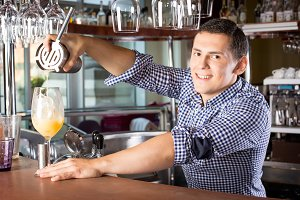 Smiling handsome bartender pouring a drink into the glass out of