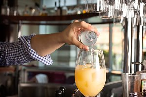 Bartender's hand holding a botlle with alcohol drink and puring