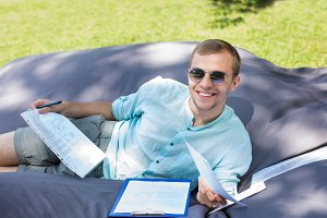 Happy smiling young student is studying outdoors, laying on a la