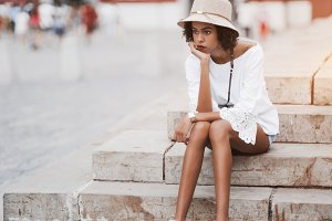 Tired black tourist girl outdoors