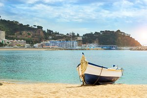 Fishing boat moored on sandy beach. Blanes, Spain