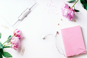 Feminine workspace with empty paper and pink peons