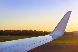 Wing of aircraft over the runway at sunset. Riga