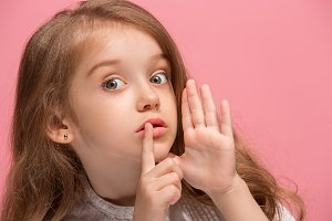 The young teen girl whispering a secret behind her hand over pink background