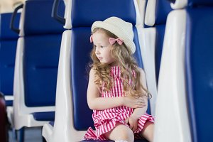 Happy little girl sitting in front of her mom in an empty train car looking to the side