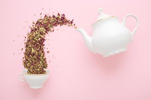 Dry tea pouring from teapot & cup