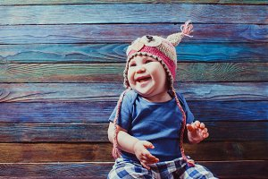 Smiling baby in cute crocheted owl hat