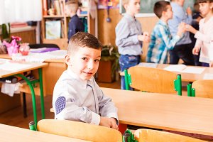 cute boy is sitting at the desk in the classrom