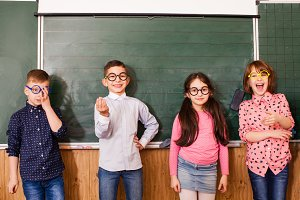 Cool pupils in glasses have fun together during the break