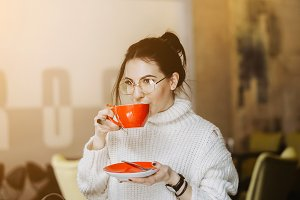Woman in glasses enjoys a hot drink