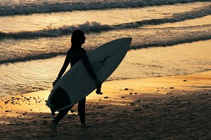 girl surfer on seashore at sunset