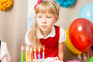 little girl is thinking about the wish  on her birthday