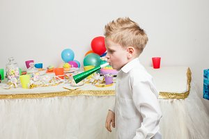 cute boy is celebraiting birthday party with cake and presents