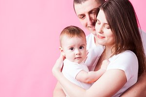 Cute baby in parent's arms looking at the camera