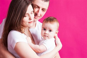 Beautiful family is posing with their infant, pink background