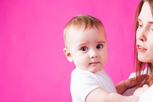 Infant baby looking at the camera, pink background