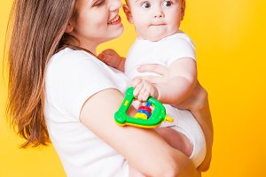 Pretty woman with a small baby in her arms on the yellow background