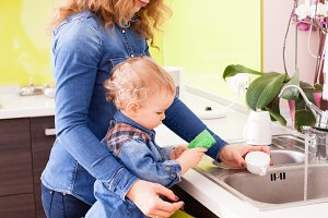 Young mother with a baby boy washing dishes