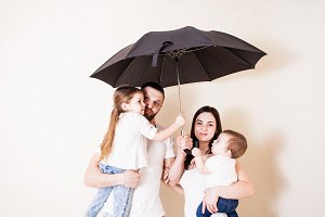 Young family standing under umbrella