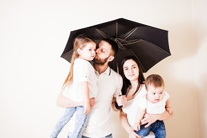 Attractive family standing under umbrella