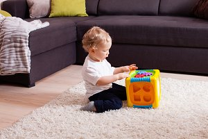 Baby boy playing with plastic sorter toy
