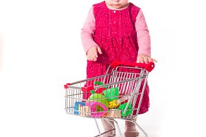 Cute baby girl playing with toy shopping cart.