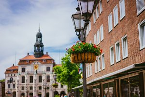 Vintage street light lantern with flowerbed. Historic town hall on the background in Lueneburg Germany