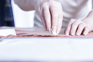 dressmaker marking a fabric