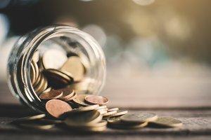 Coins on glass jar on table