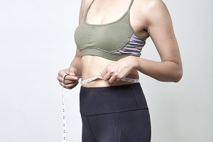 Woman measuring shape of beautiful waist