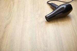 black hair dryer on wood background.