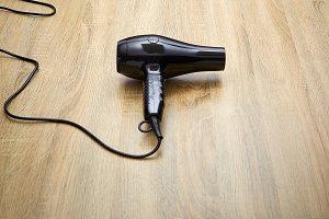 black hair dryer on wood background.