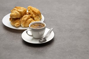 Cup of fresh coffee with croissants