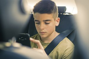 child with mobile phone in the car