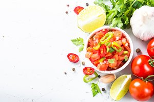 Salsa sauce and ingredients on white.