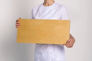 doctor girl in a white robe stands with a wooden sign