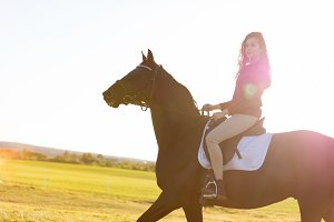 Young girl riding a dark horse in a field on a sunset