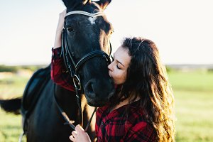 Young girl kissing bay horse's muzzle.