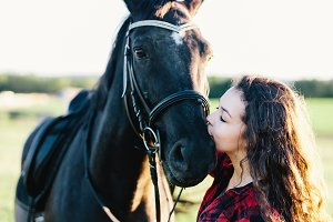 Black horse kissed by a young woman.