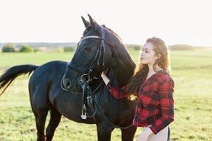 Young girl standing next to a beautiful dark horse.