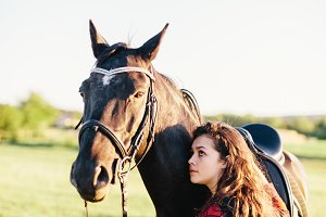 Young girl hugging purebred black horse on the field.