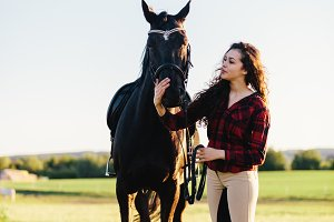 Young woman dressed casually petting black horse