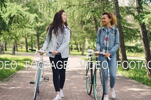 Sporty young women are walking in park with bicycles and chatting enjoying beautiful fir trees and warm spring day. They are wearing trendy denim garments.