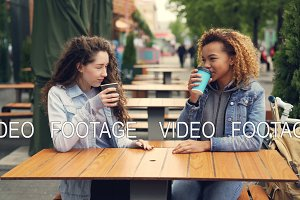 Two young women are drinking coffee and talking sitting at table in outdoor cafe in park, young women are having fun and laughing. Conversation and drinks concept.